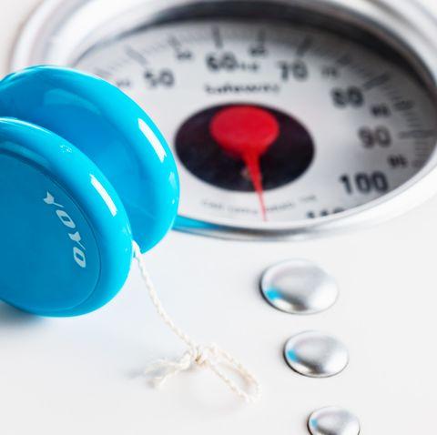 Yo-yo balancing on scale: metaphor for juggling act of dieting
