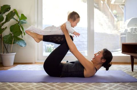 Side View Of Happy Woman Playing With Baby While Exercising At Home