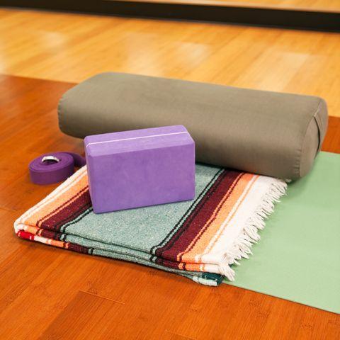 yoga mat, blanket, bolster, block and strap on studio floor
