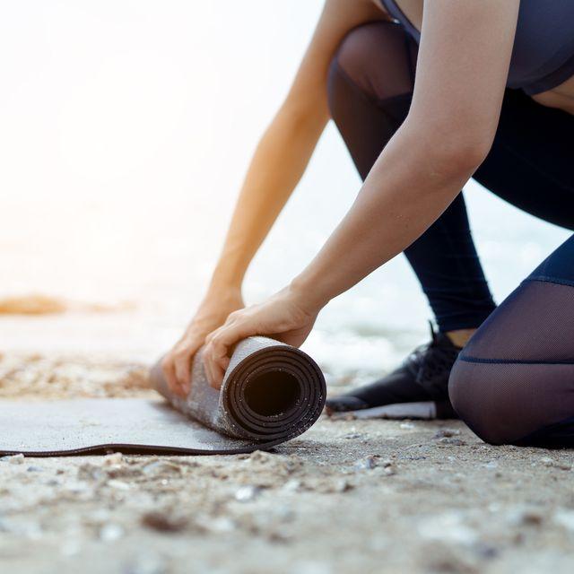 mujer extendiendo una esterilla de yoga en la playa