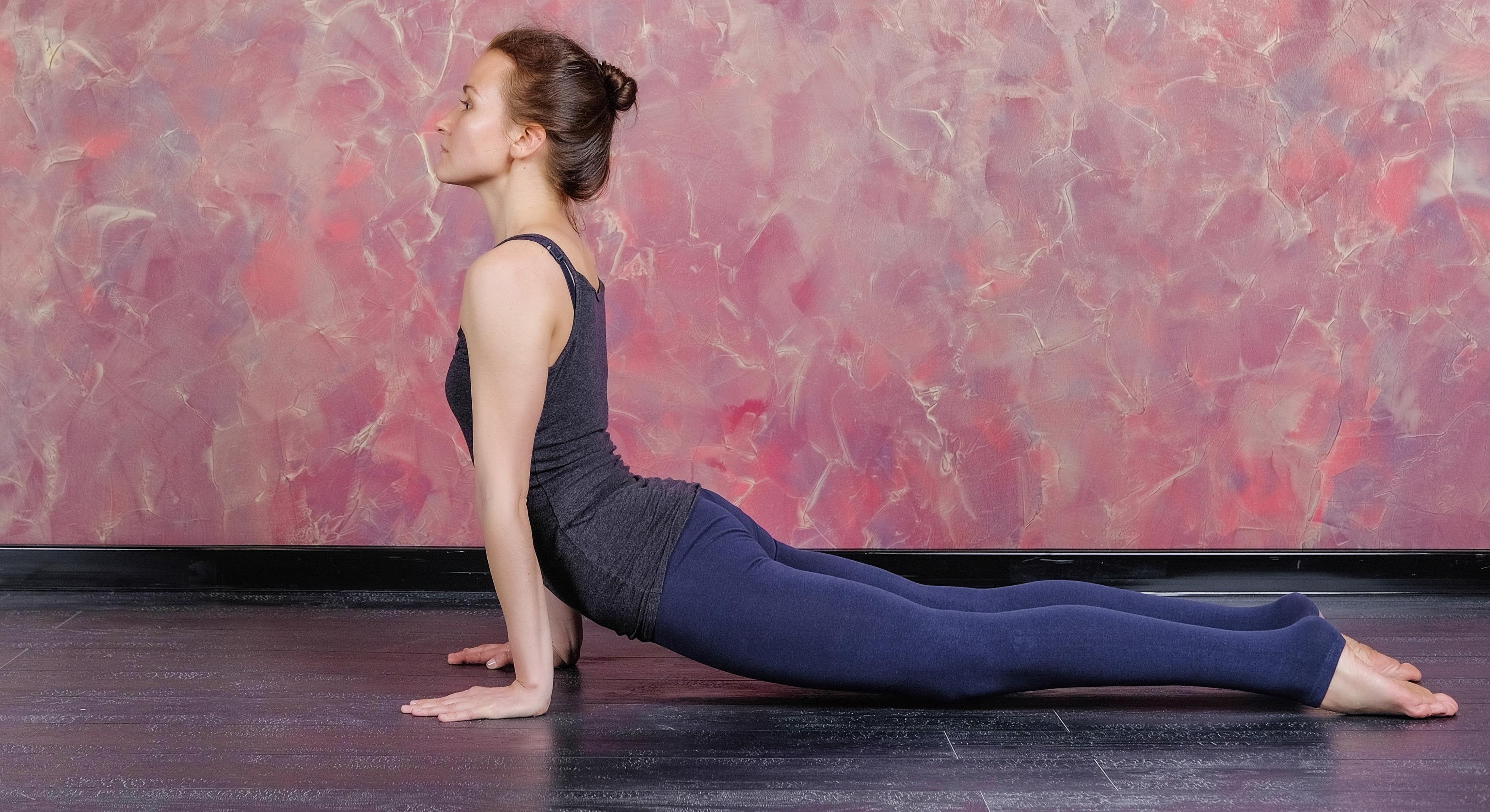 Woman practicing and stretching in a yoga studio. Basic yoga pose: upward facing dog or urdhva mukha svanasana.
