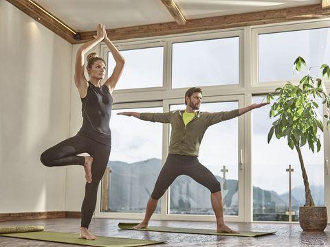 Casal praticando ioga em uma sala com janela panorâmica