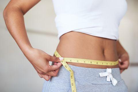 mujer midiendo los centímetros de su cintura