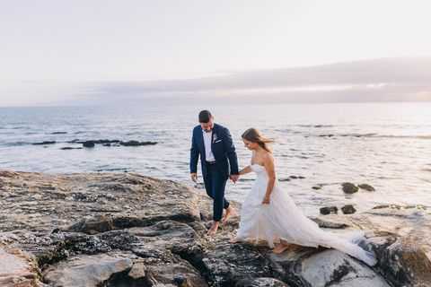 young adult couple in wedding dress and suit walking on the cliffs on the coast of porto, portugal