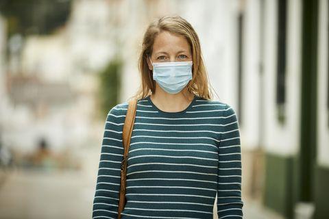mujer con mascarilla pasea por la calle en plena pandemia por covid 19