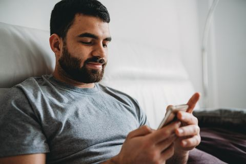 young adult man using his smartphone sitting on the sofa