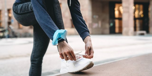 young adult woman tying his shoes in the city