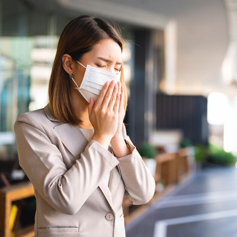 young asian business woman wearing surgical mask and coughing while walking in public in coronavirus or covid 19 spreading situation