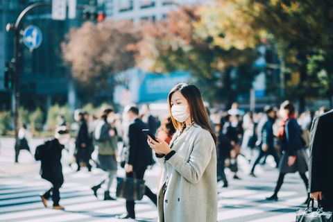 young asian businesswoman commuting in busy downtown city street with protective face mask and using smartphone to protect and prevent from the spread of viruses during covid 19 health crisis