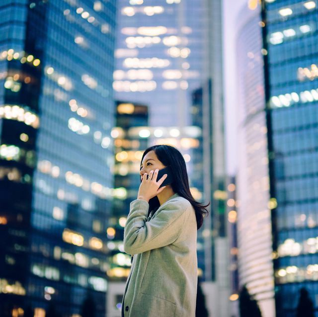 young asian businesswoman talking on mobile phone outside illuminated highrise corporate buildings in financial district
