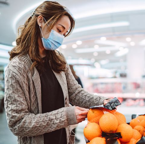 young asian lady in medical face mask shopping in a supermarket