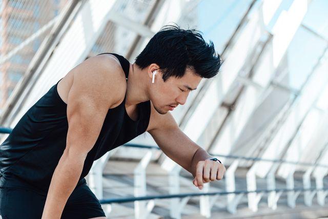 un corredor asiático mirando un reloj deportivo y escuchado música con auriculares blancos
