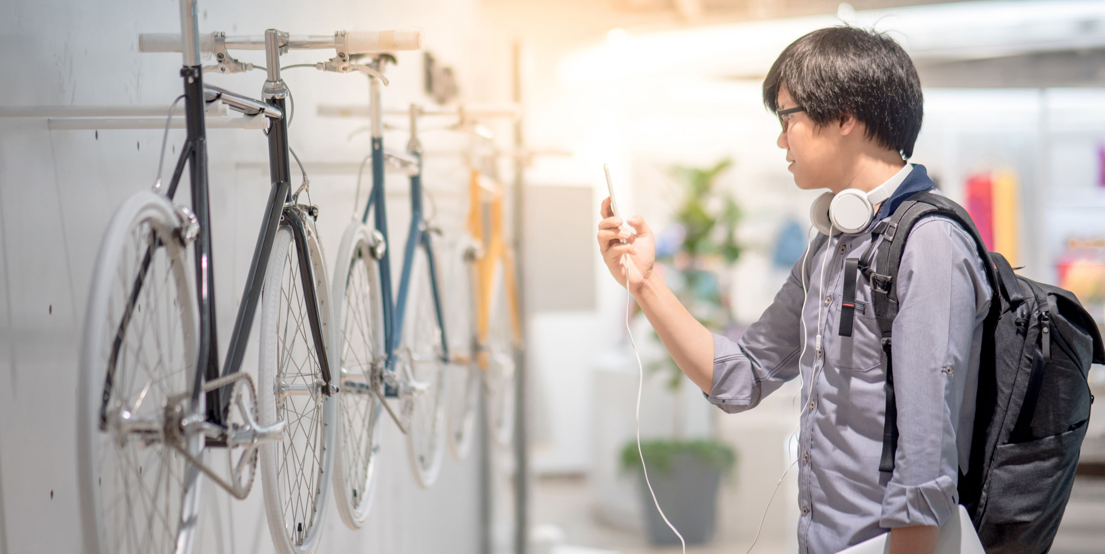 Young Asian man take a photo of vintage bicycle at bike shop in department store by smartphone