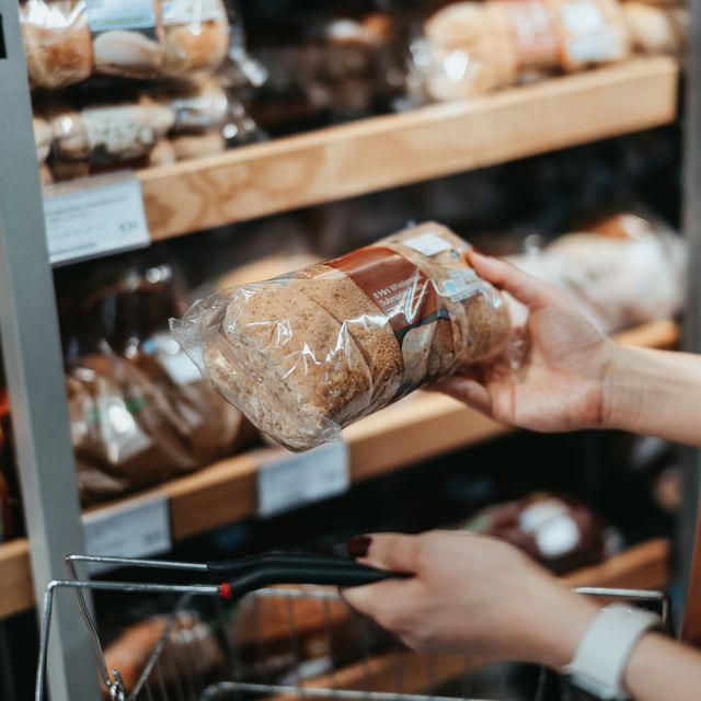 mujer eligiendo pan en el supermercado