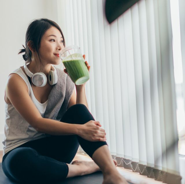 young asian woman drinking green smoothie after yoga