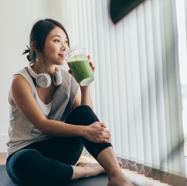 best pre workout meals woman drinking green smoothie on yoga mat