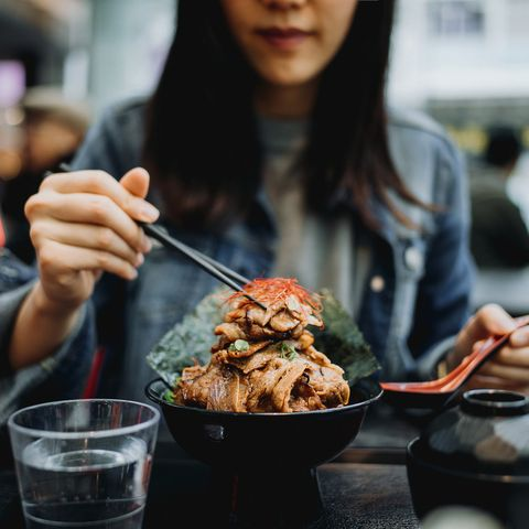 young asian woman eating grilled beef rice bowl with chopsticks joyfully at japanese restaurant