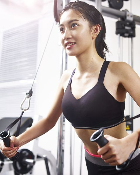 young asian woman exercising in gym using equipment