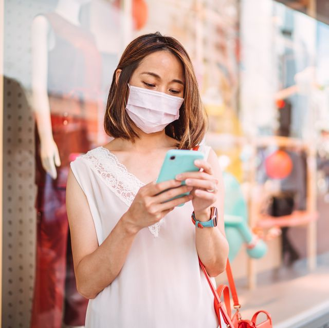 young asian woman in medical face mask using smartphone while standing in shopping district of city