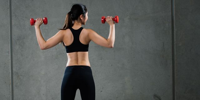 a young asian woman is training dumbbells