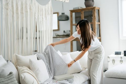 young asian woman organising and tidying up the cushions and throw on the sofa in the living room at home