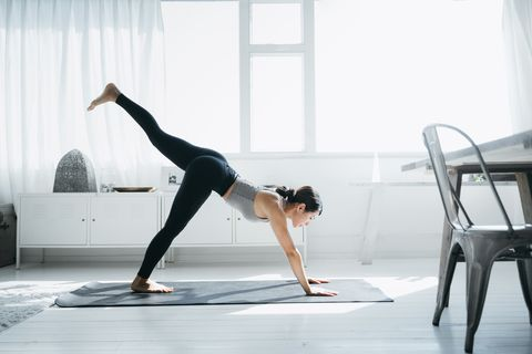 young asian woman practicing yoga in the living room at home in the morning