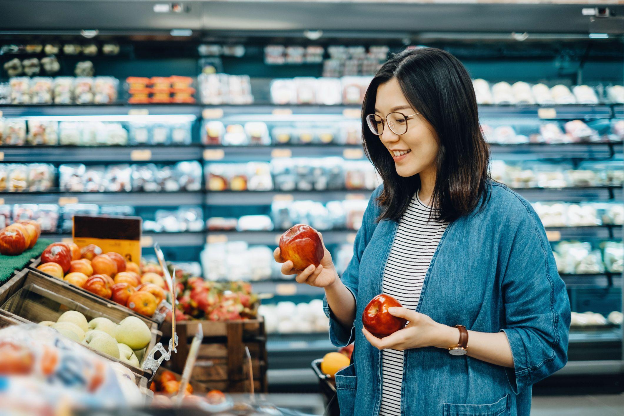 Young Asian woman shopping for fresh organic fruits in supermarket