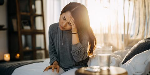 young asian woman sitting on the bed feeling sick and suffering from headache, a glass of water and medicine on the side table
