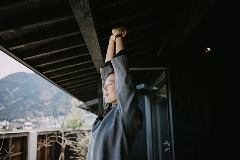 young asian woman standing on the balcony on a fresh bright morning relaxing and stretching with her eyes closed