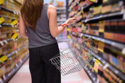 young asian woman with food basket at grocery store or supermarket