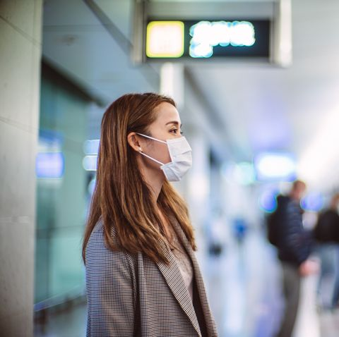 young asian woman with protective face mask commuting in the city and waiting for train in platform