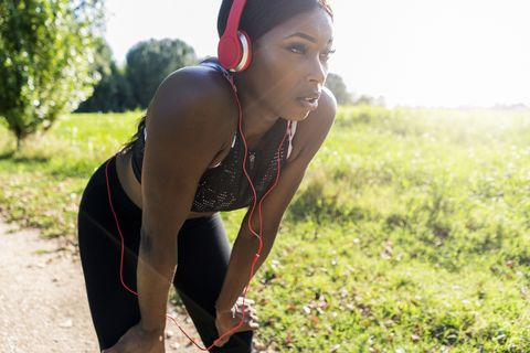 young athlete in nature, listening music with headphones, preparing for training