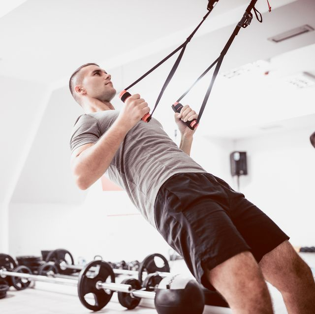 young athlete men doing back exercise with suspension straps in gym