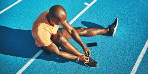 Young athlete tying up his shoes on a running track