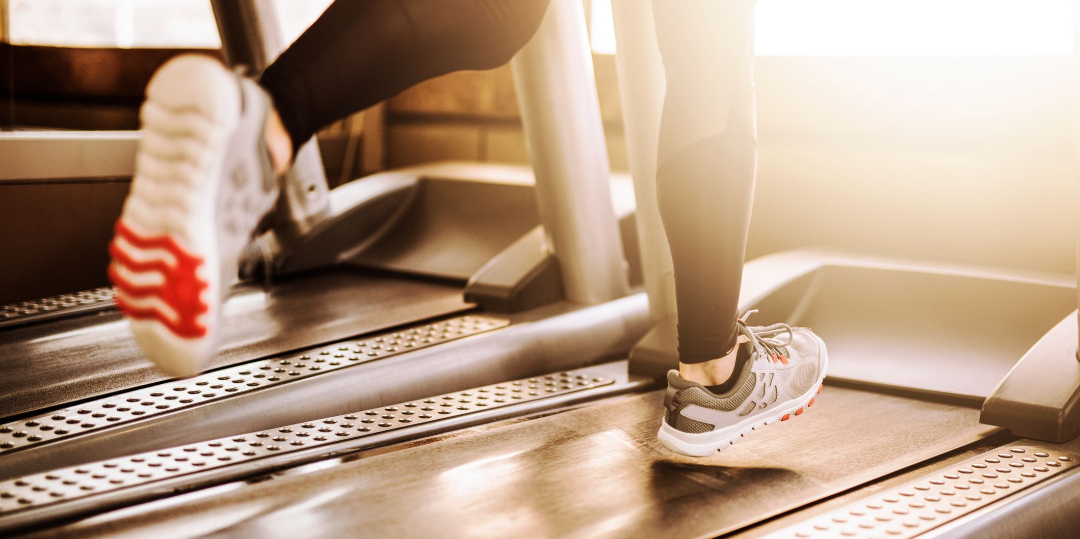 Young athletic man running on treadmill legs close up
