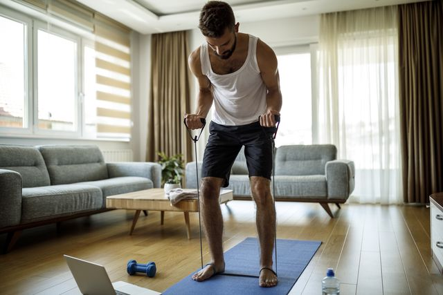 young athletic man training with resistance bands at home