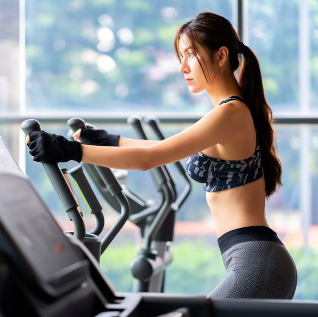 young athletic woman exercising on cross trainer machine cardio training at the gym