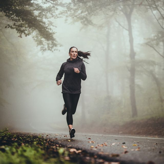 young athletic woman jogging on the road in foggy forest