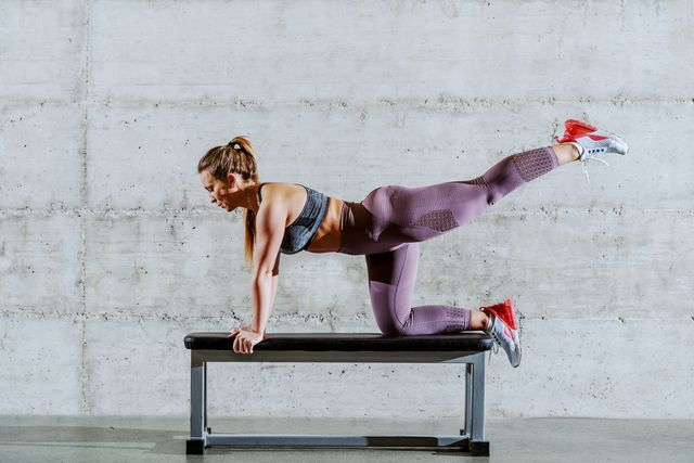 young attractive caucasian fit sporty brunette in sportswear and ponytail doing cross over pulses on bench
