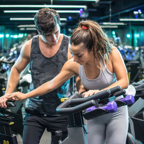 Young attractive woman with handsome trainer setting up exercise bike before cycling workout in gym
