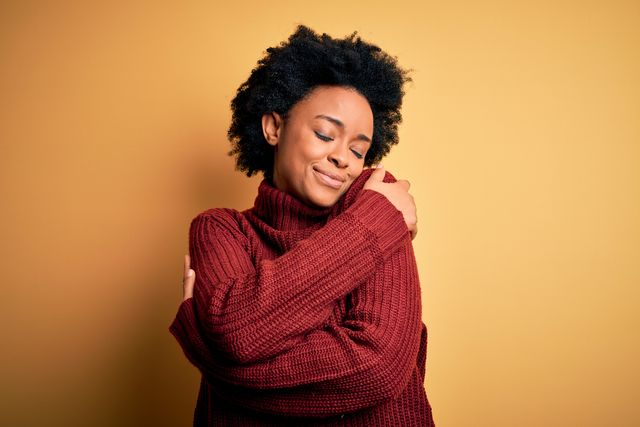 young beautiful african american afro woman with curly hair wearing casual turtleneck sweater hugging oneself happy and positive, smiling confident self love and self care