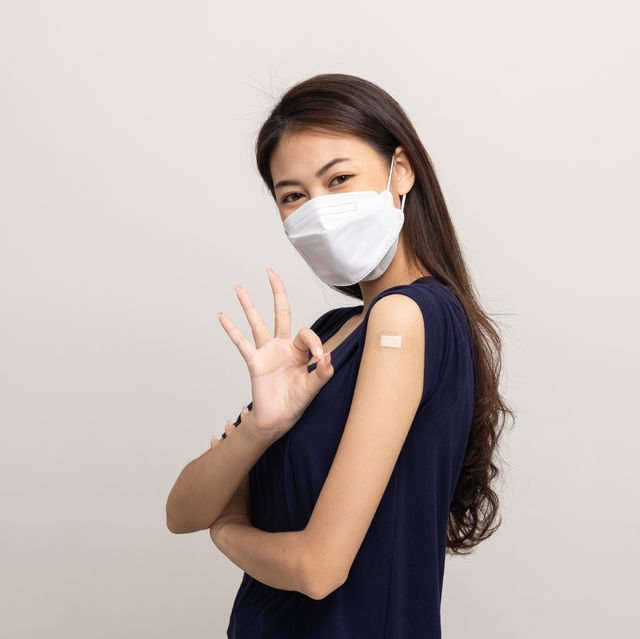 young beautiful asian woman wearing mask and getting a vaccine protection the coronavirus happy female showing arm after receiving vaccination on isolated white background