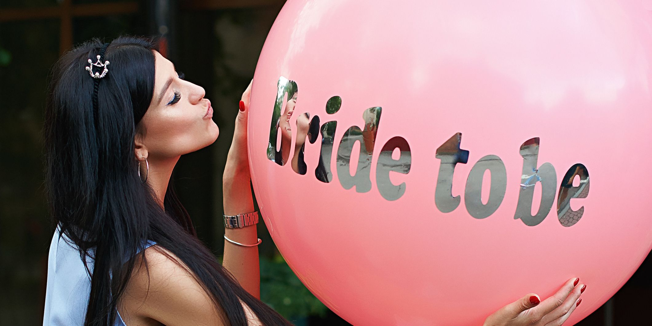 Young beautiful brunette bride to be with dark hair and silver crown on it kissing her pink bachelorette party balloon