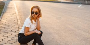 Young beautiful stylish hipster woman with sunglasses in a white polo shirt and black jeans with sneakers sitting on the street at sunset. Fashionable girl in summer clothes