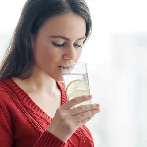 young beautiful woman in red sweater with glass of water with lime, woman stands near window in skyscraper on cloudy day healthy drink, natural antioxidant, vitamins in urban life