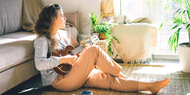 young beautiful woman plays ukulele, sings in the sun