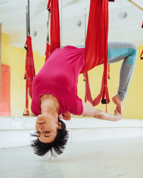 young beautiful woman practicing yoga fly with a hammock in the bright studio the concept of mental and physical health