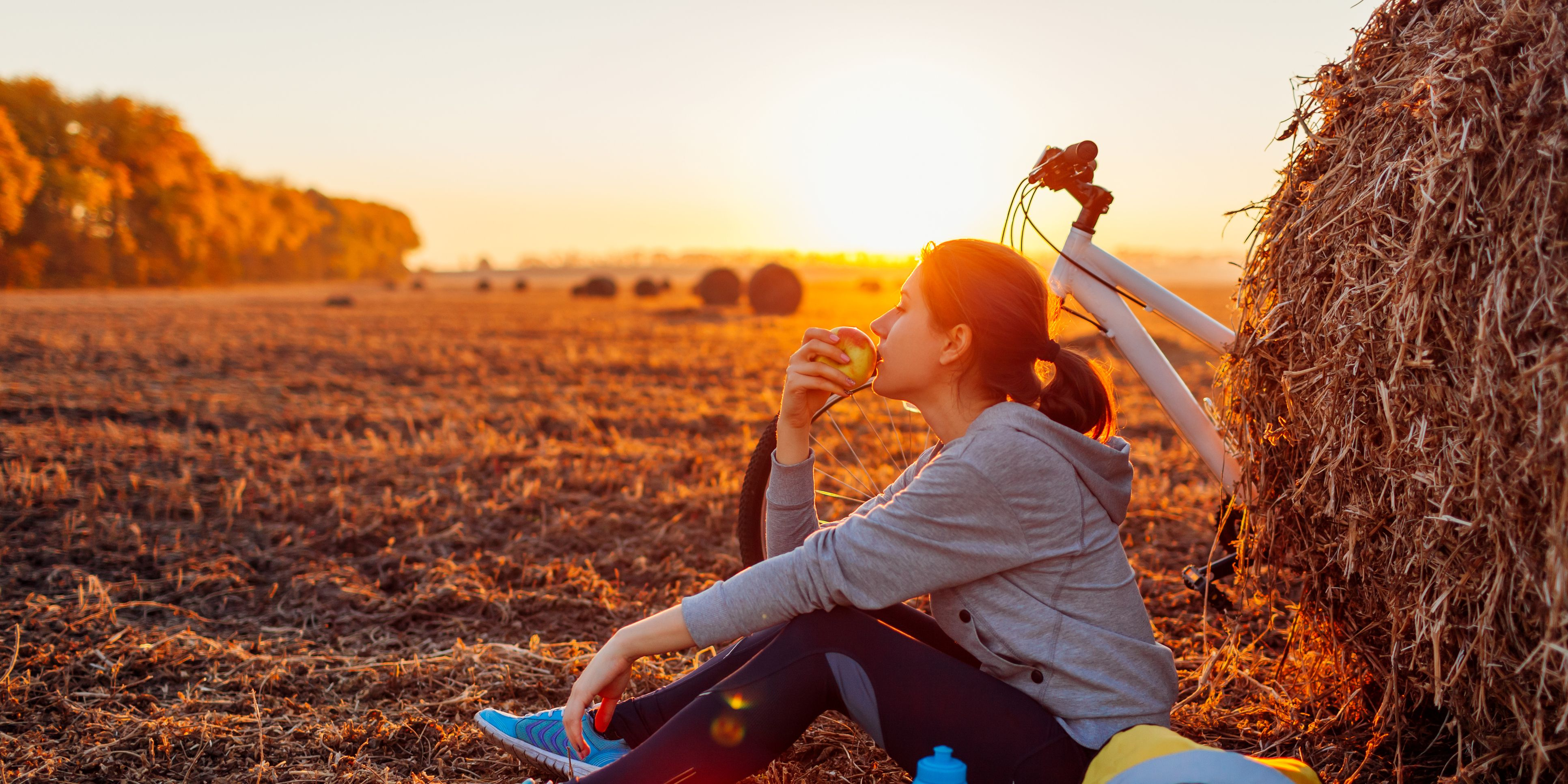 Young bicyclist having rest after a ride in autumn field at sunset. Woman eating by haystack