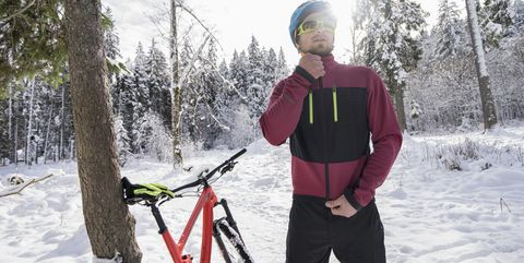 Young biker wearing zipper jacket by bicycle in snow