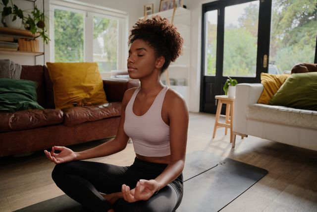 young black woman doing yoga at home in the lotus position